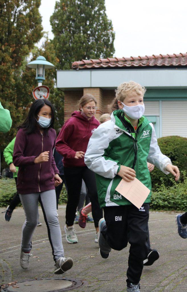 Läuferinnen und Läufer mit Mund-Nasen-Bedeckung beim Sponsorenlauf am Rupert-neudeck-Gymnasium 2020.